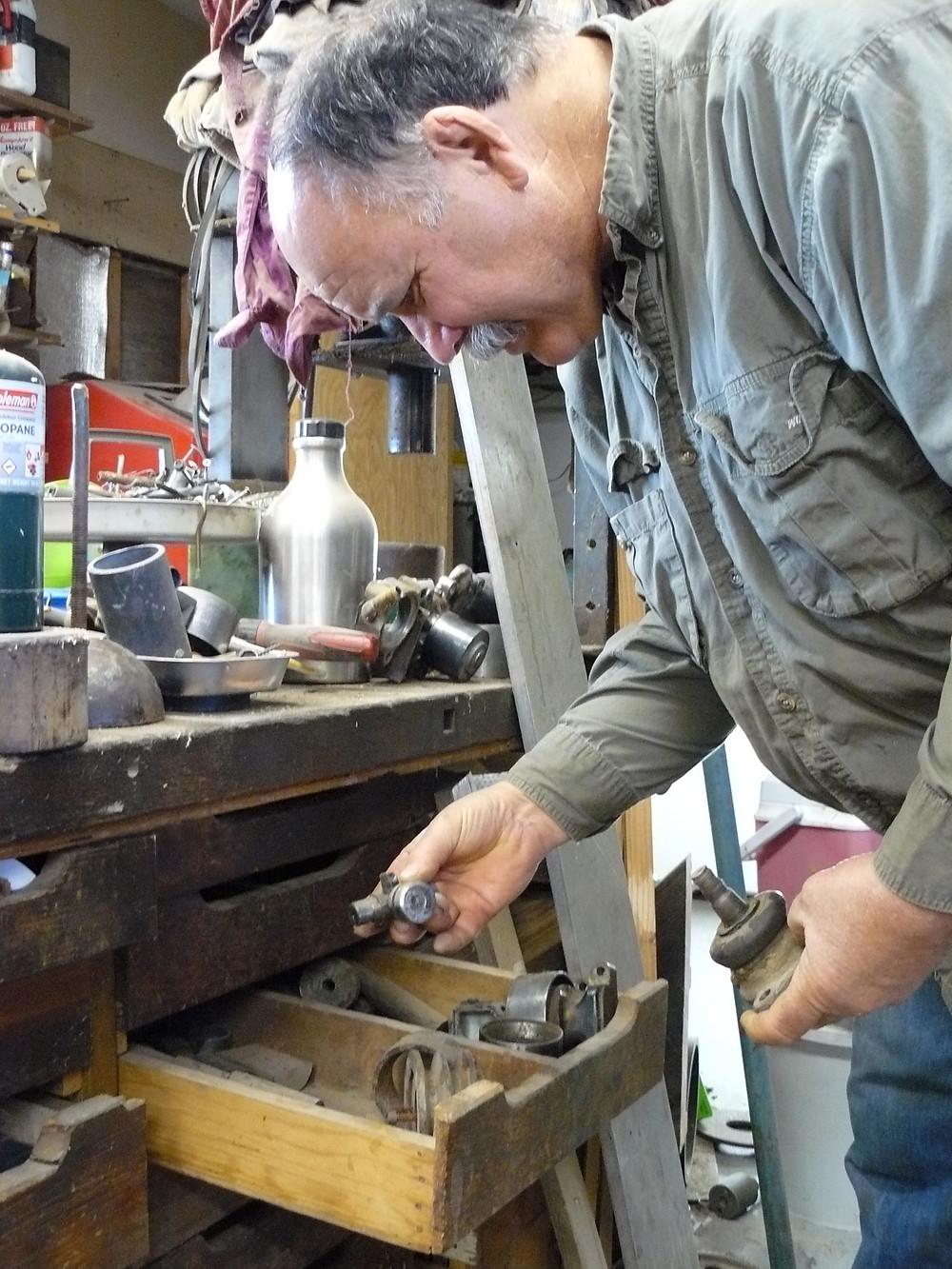 David Crawford going through workbench drawer full of small metal things