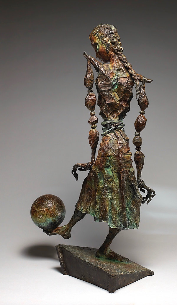 Bronze girl sculpture in skirt and balancing a soccer ball on her bare foot.
