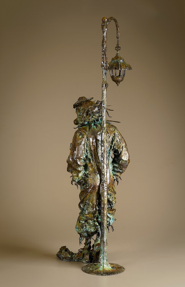 Bronze clown leaning against a light post.