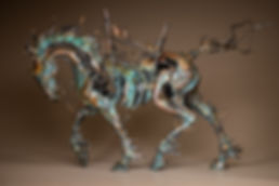 Bronze horse skeleton with small birds riding on the stick saddle.
