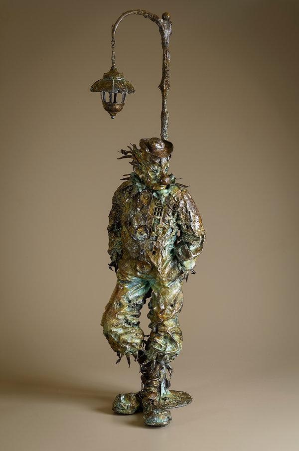 Bronze sculpture of an august clown leaning against a light post.