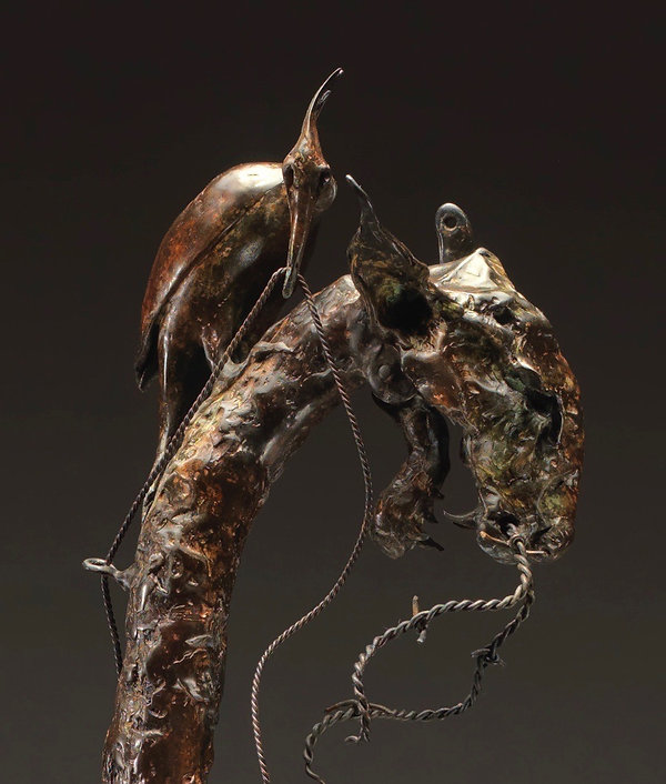Detail of the head of a cat sculpture with a woodpecker sitting on it, wiring it together.