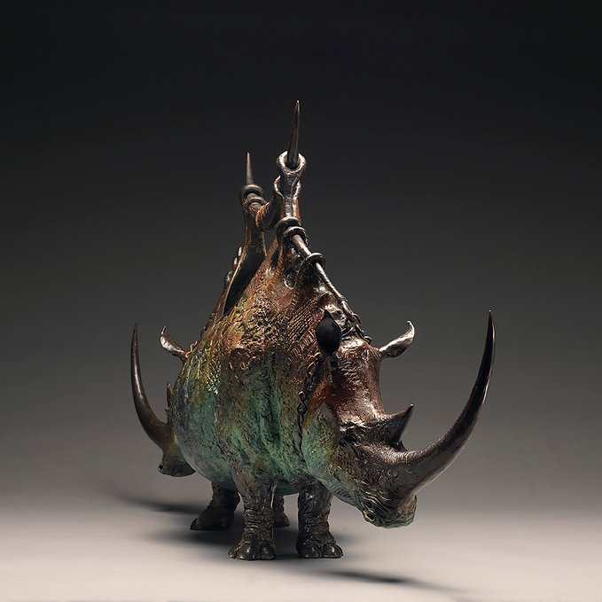 Bronze vessel conprised of the front half of two rhinos with a handle joining the shoulders.