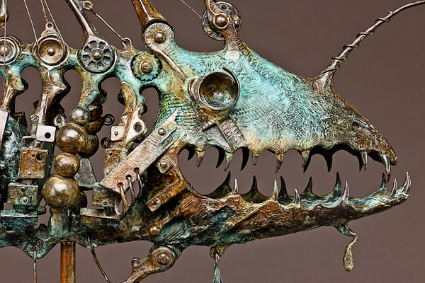 Head detail of angler fish sculpture consisting of a fish skeleton and fishing gear.