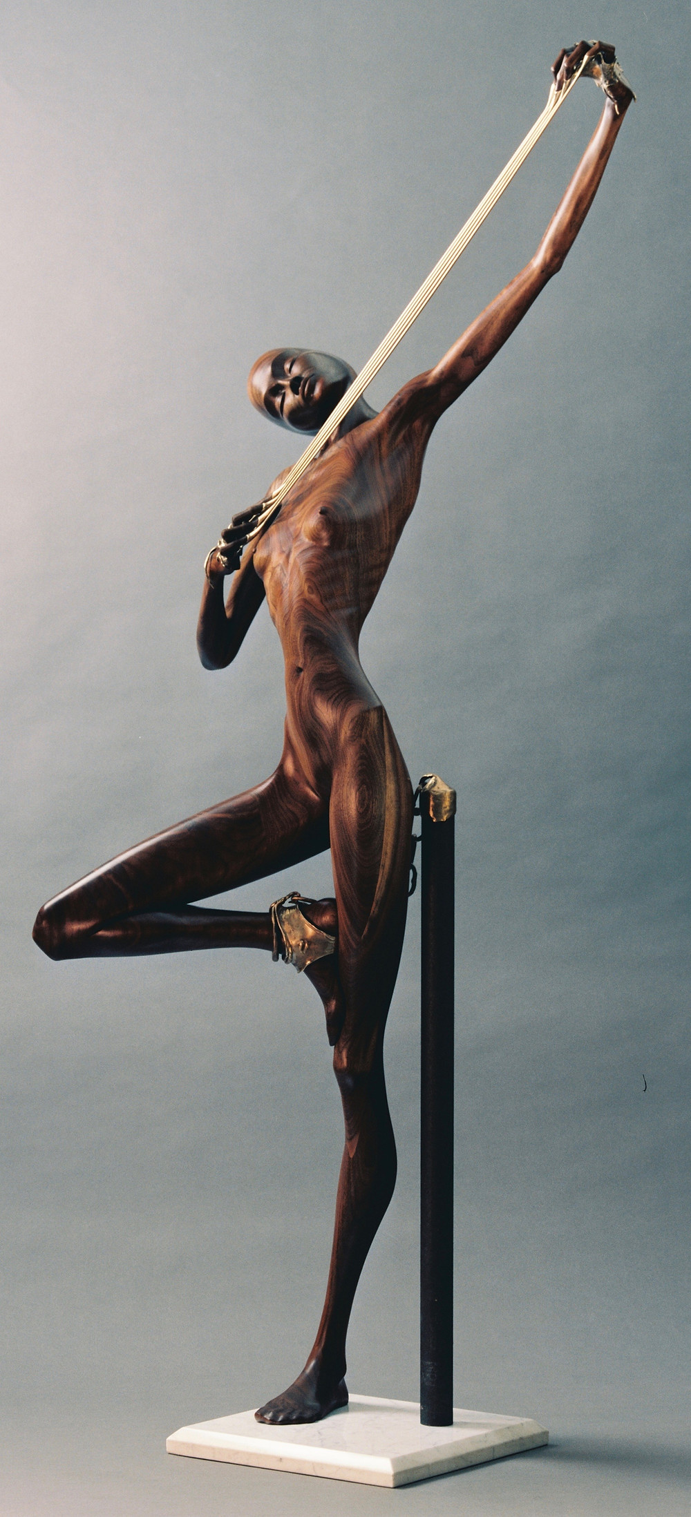 Life-size, walnut, female figure stretching bronze between her fingers, standing with one foot on opposite knee.