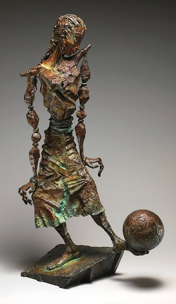 Bronze sculpture  of a young girl with a soccer ball balanced on her foot.