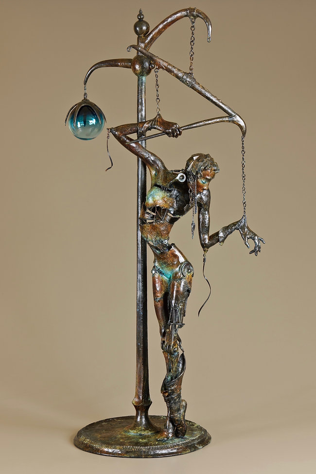 Bronze female sculpture of a marionette who controls herself.