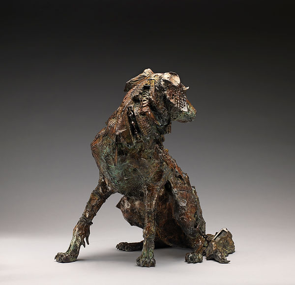 Bronze sculpture of a Border Collie dog with its body wired and patched together.