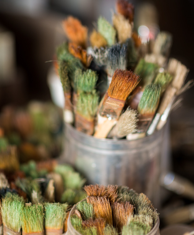 containers of used colorful paintbrushes