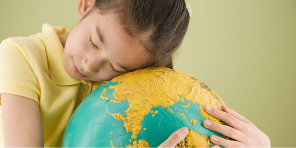 A child lovingly embracing a globe