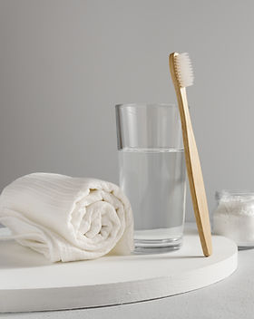 Bamboo toothbrush, glass of water, white a cotton towel and powder for brushing your teeth