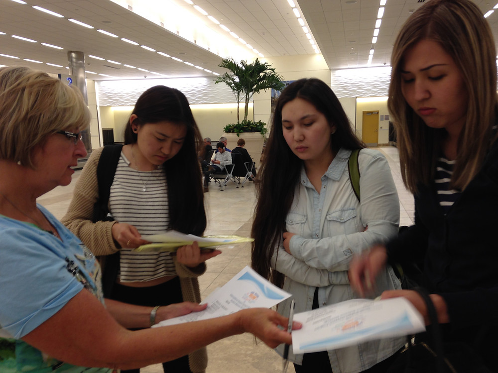 A volunteer gives safety orientation schedules to students at the airport.