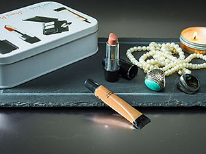 Cosmetics gift set in a tin can and lip stick, eye cream, candle and accessories