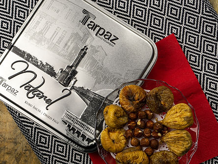 Square Tarpaz tin box next to a bowl of dried figs and hazelnuts