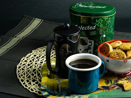 Elite coffee tin, french press, some cookies and a cup of coffee on a tin tray