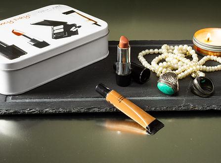 Teneke kutu içerisinde gelen kozmetik seti ve yanında ruj, göz altı kremi, mum ve aksesuarlar