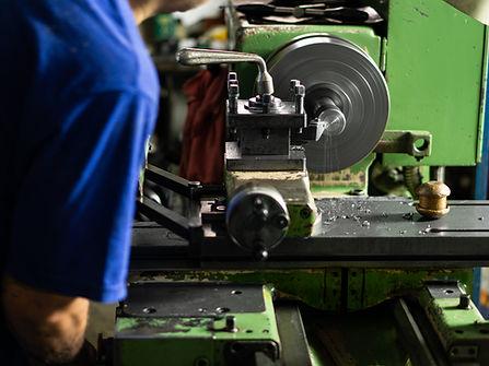 Teksan technician running lathe machine working on a tin can tooling