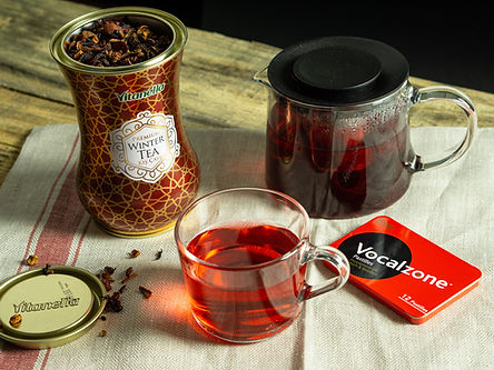 Vitanella glass shaped tea tin, Vocalzone pastille tin case, a glass of tea and a tea pot on a wooden table