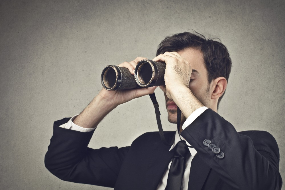 business man with binoculars looking to the future of insolvency