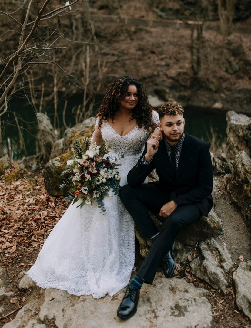 Gia and Kerwin holding Winter Bridal Bouquet sitting on a rock in the woods