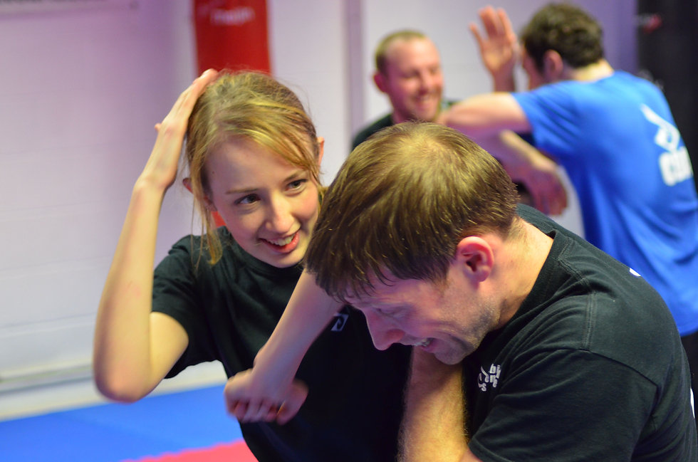 A female engaging a male with elbow strikes in a self defence class