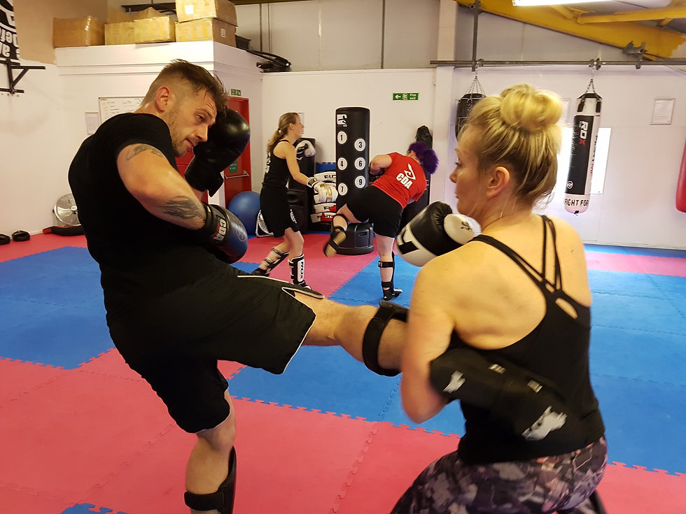 Two students sparrng at friday night fight club kickboxing session cheltenham
