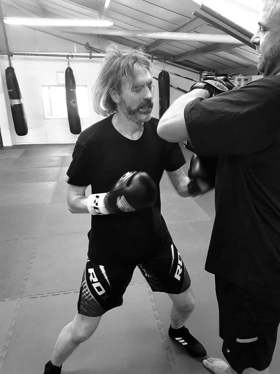 Image of a CDA student hitting some focus mitts in  a self defence class