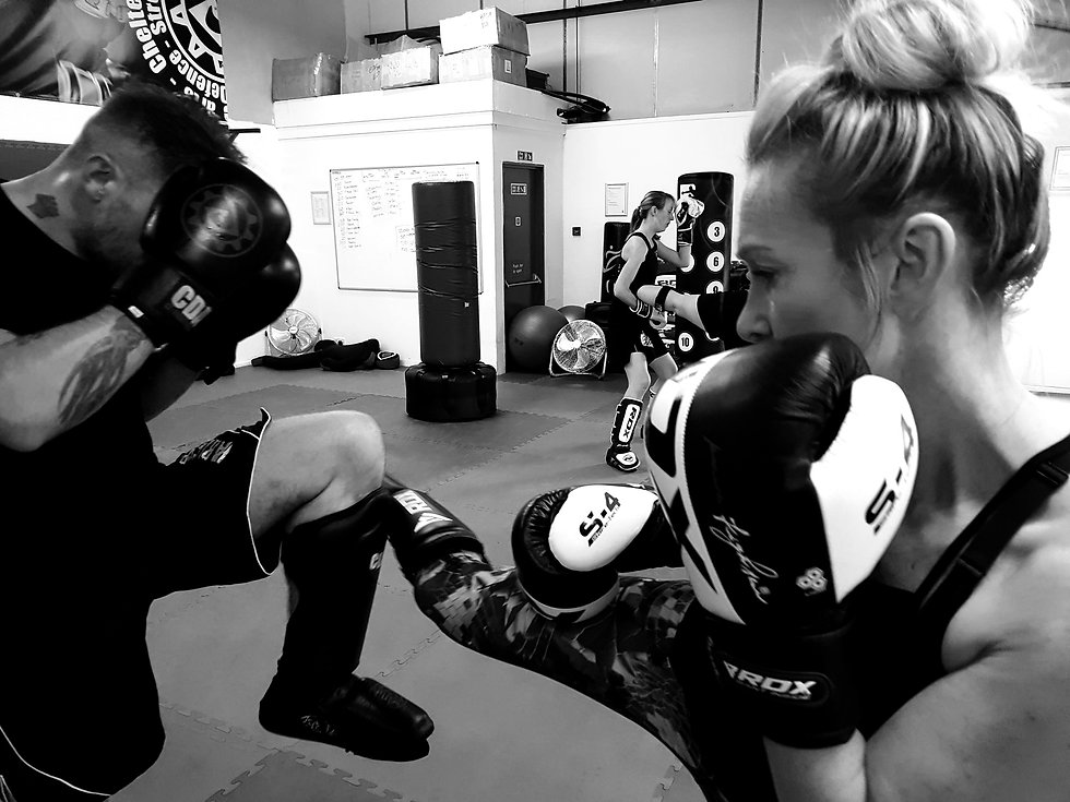 A kickboxing student throwing a turning kick, being leg checked by their opponent
