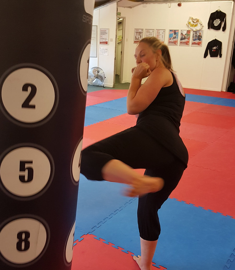 Lady hitting a kickbag