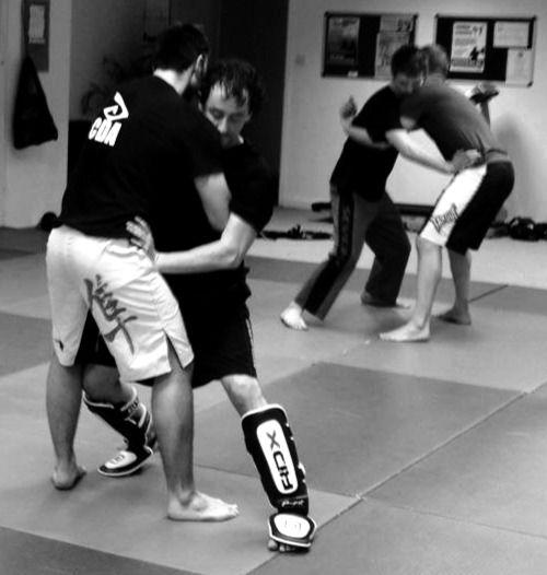 Kickbxing students practicing clinch at a muay thai seminar.
