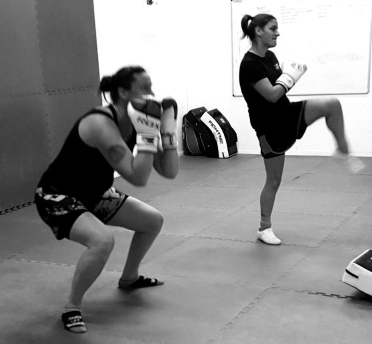 Two kickboxing students in the middle of a fitness esection of a class