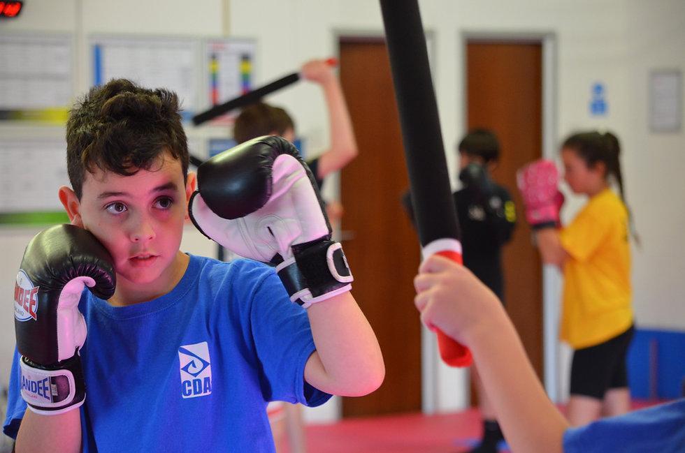 CDA Junior Kickboxing and martial arts student in a kickboxing training drill
