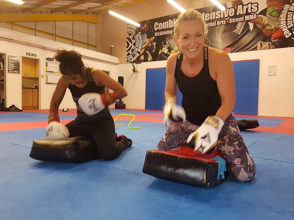 Two students hitting bags getting fit
