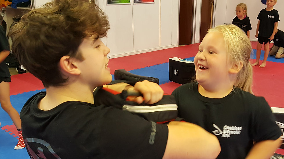 Girl and instructor enjoying hitting the pads
