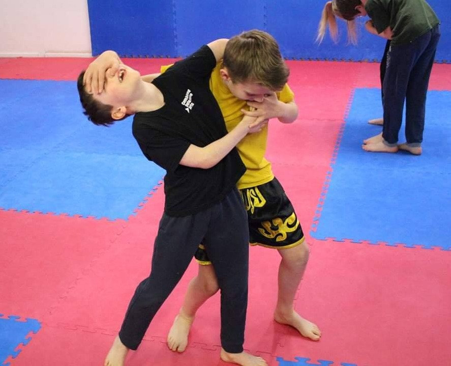 Two Junior children wrestling in a self defence marial arts session