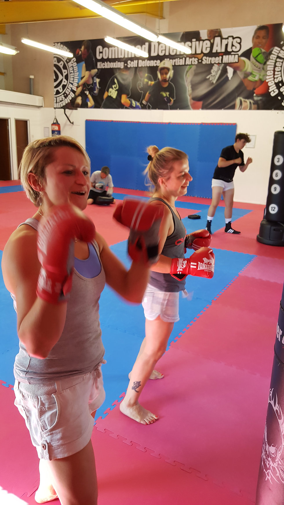 Two ladies having fun and working out in a fitness kickboxing class