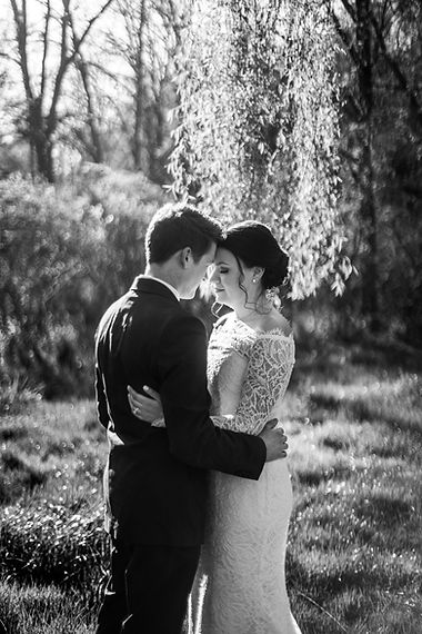 Edited black and white bride and groom embrace under willow tree at Piney Branch Golf Course wedding in Maryland