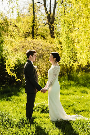 Bride and groom hold hands under a willow tree at Piney Branch Golf Club in Maryland