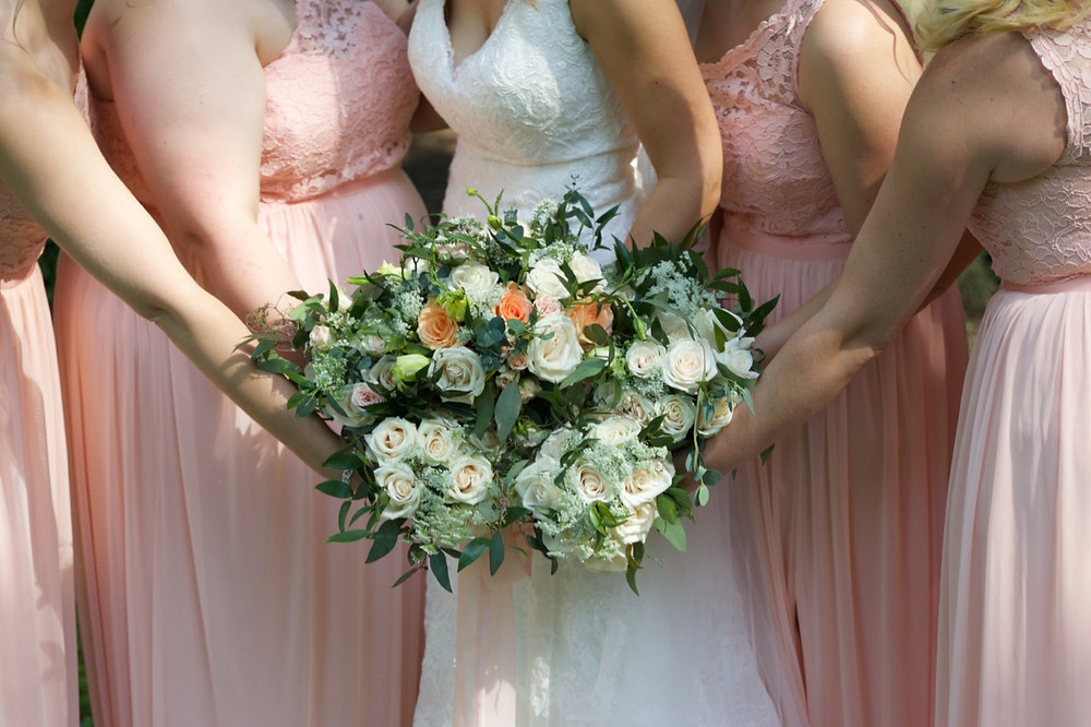 Bride and Bridesmaids hold flower bouques together in a beautiful formation.