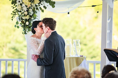 Bride and groom kiss under arbor at Piney Branch Golf Course in Maryland