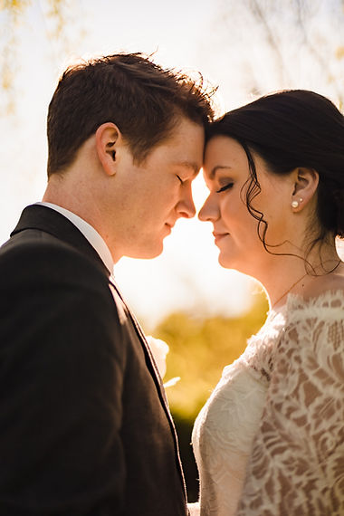 Bride and groom rest on each other's foreheads during golden hour in at Branch Golf Club in Maryland