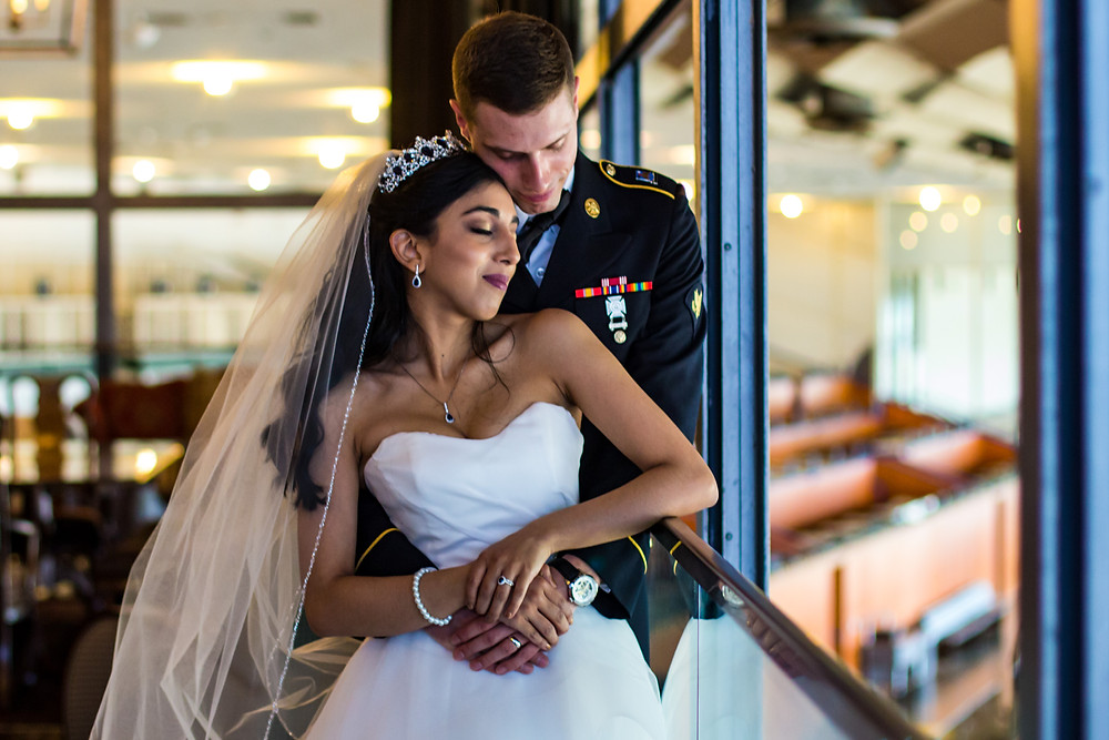Newlywed husband and wife holding each other overlooking the grandstands at Laurel Racetrack