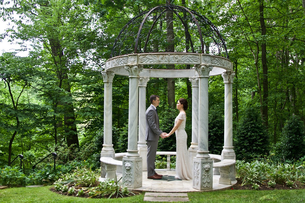 Bride and groom hold hands in the marble gazebo at Gramercy mansion in Maryland