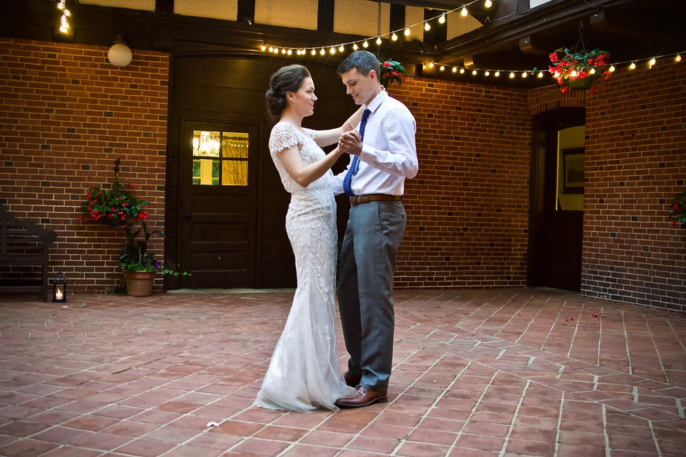 Bride and groom dance in the courtyard at the carriage house of Gramercy mansion in Maryland