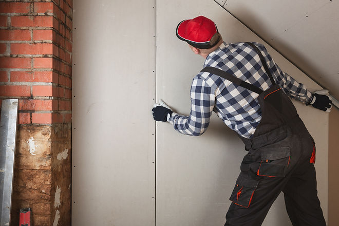 Man installing plasterboard sheet to wal