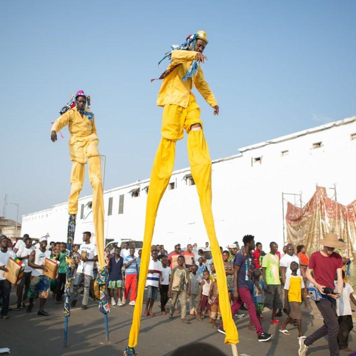 Men wearing yellow walking on sticks at a festival.
