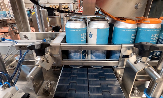 A paktech applicator applying can carriers to full beer cans