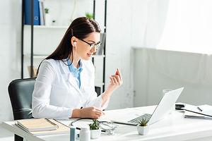 female positive doctor in earphones havi