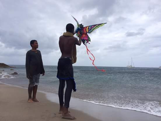 Everton being shown how to fly a kite at Little Bay