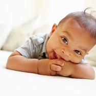 baby smiling eating his thumb.jpg